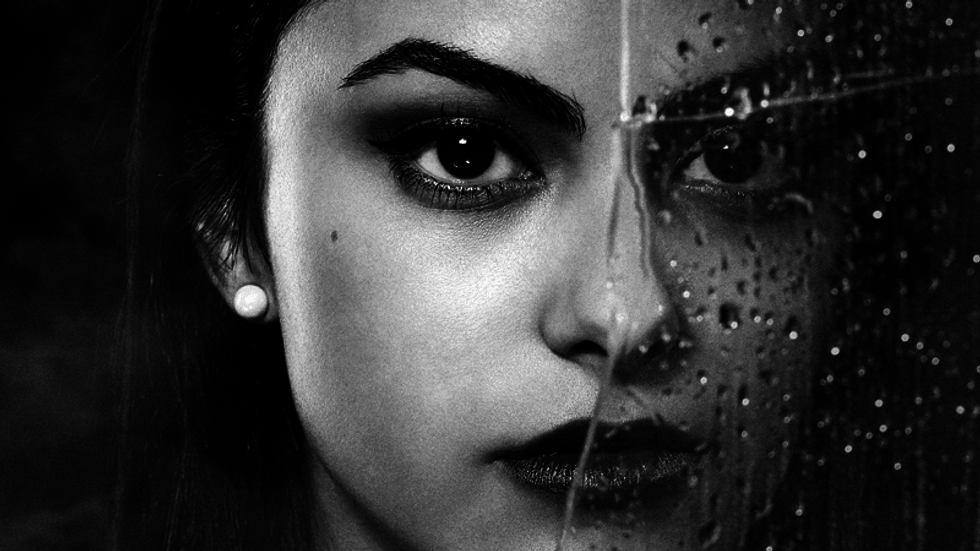 Close up of Camila Mendes with half of her face covered by rain