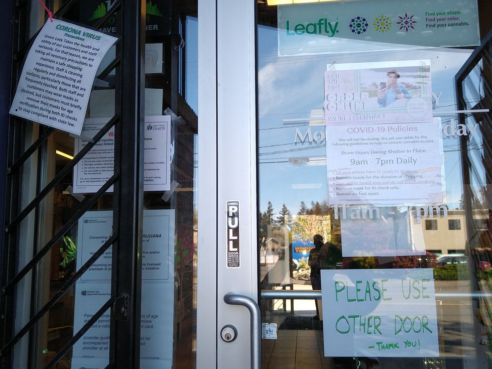 Signs in front of Green Lady West in Olympia West about online ordering and corona virus