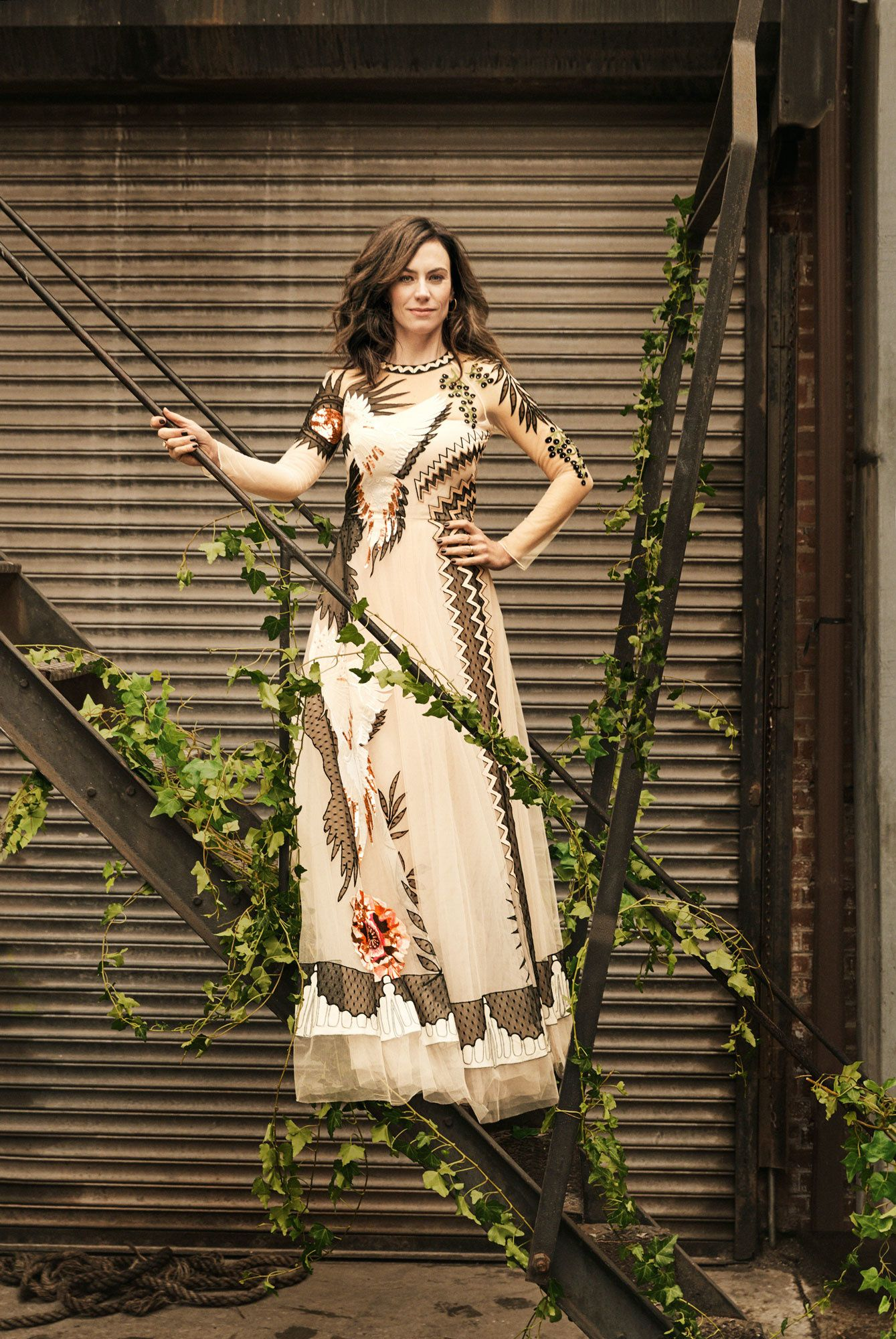Maggie Siff standing on a fire escape in a floral dress.