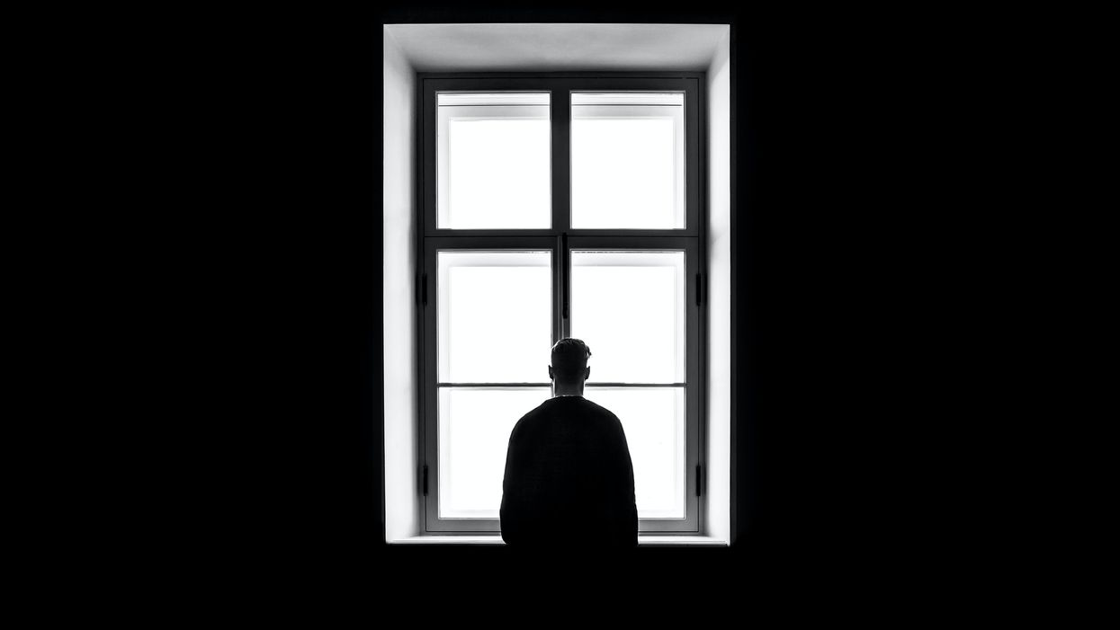man standing in dark room in front of window concept of loneliness and isolation COVID-19