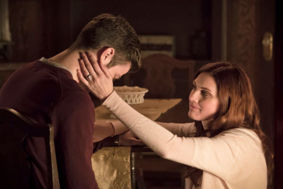 Barry Allen in a chair and having his face held by his kneeling mother Nora Allen played by actress Michelle Harrison