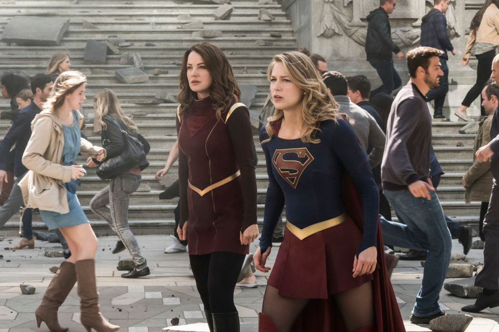 Melissa Benoist as Supergirl and her mother Erica Durance as Alura Zor El standing side by side as people rush around them
