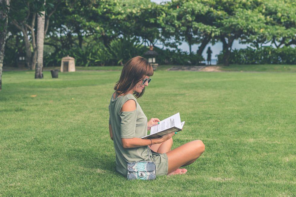 Girl reading a book in her backyard
