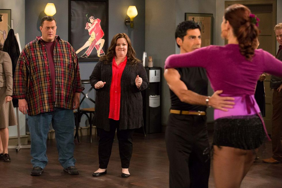 Billy Gardell and Melissa McCarthy look uncomfortable at a dance class as they watch other dancers.