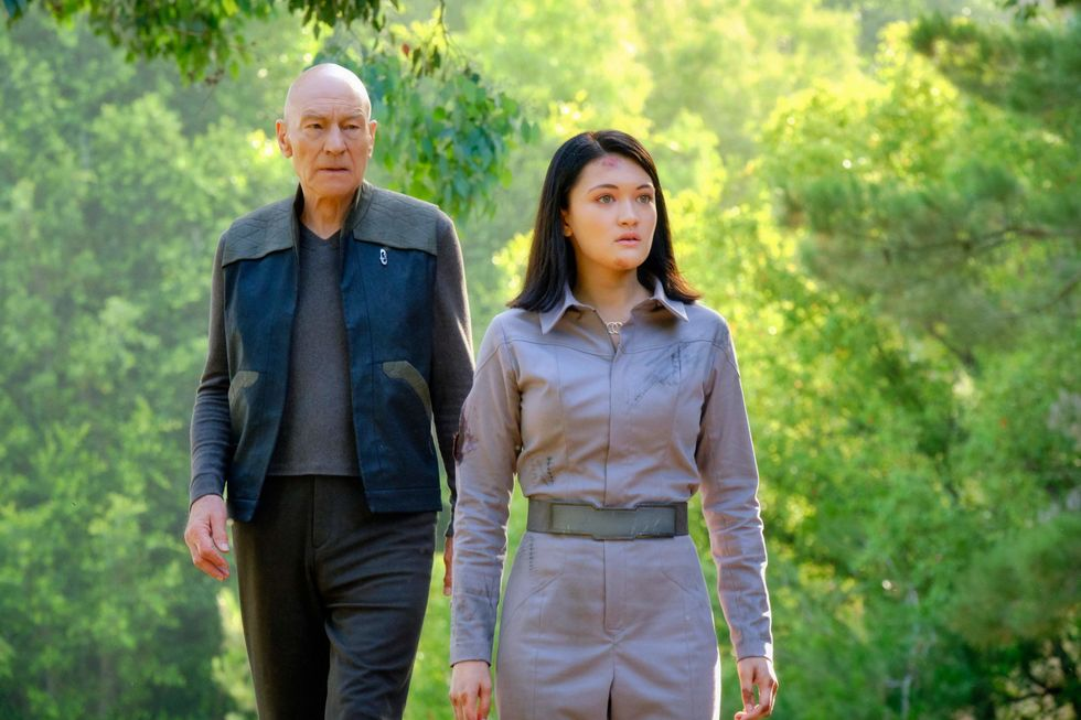 Actress Isa Briones walks with Patrick Stewart on a forested scene.