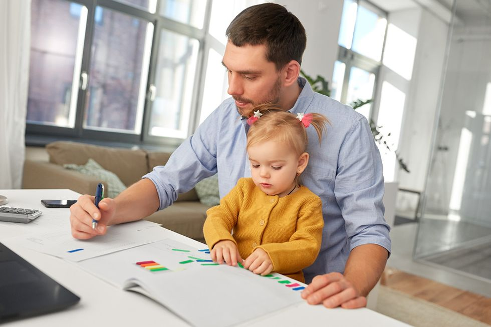 Businessman works on his daily work tasks, while taking care of his child.