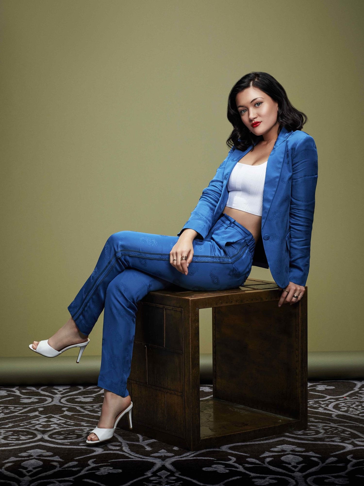 Actress Isa Briones reclines in blue silk jacket and pants.
