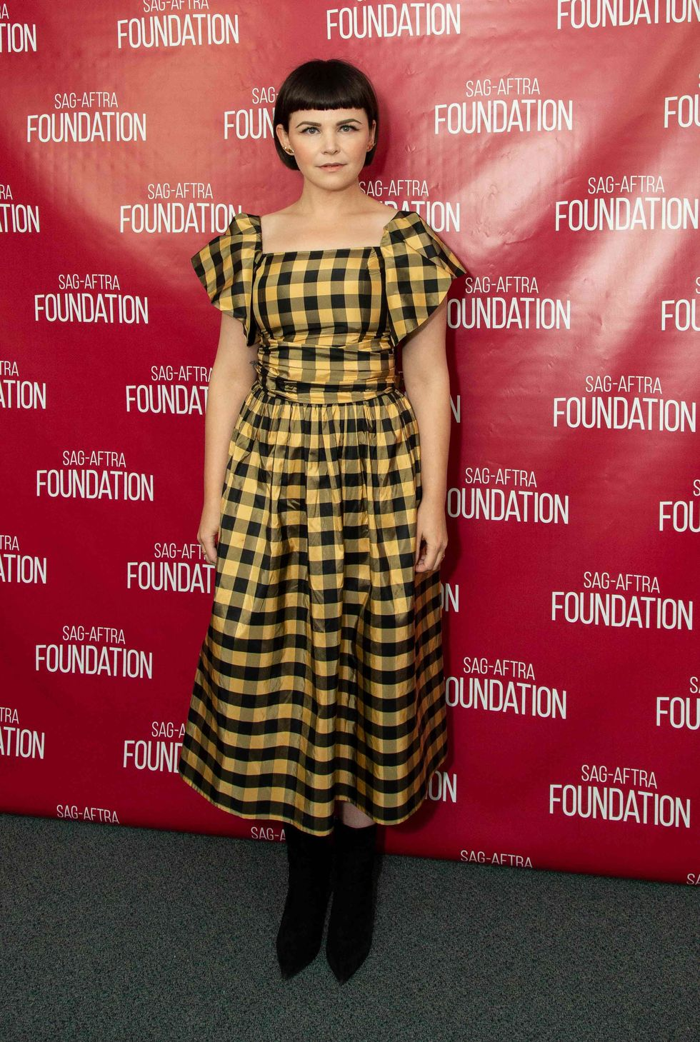 Ginnifer Goodwin in a yellow and black plaid print dress.