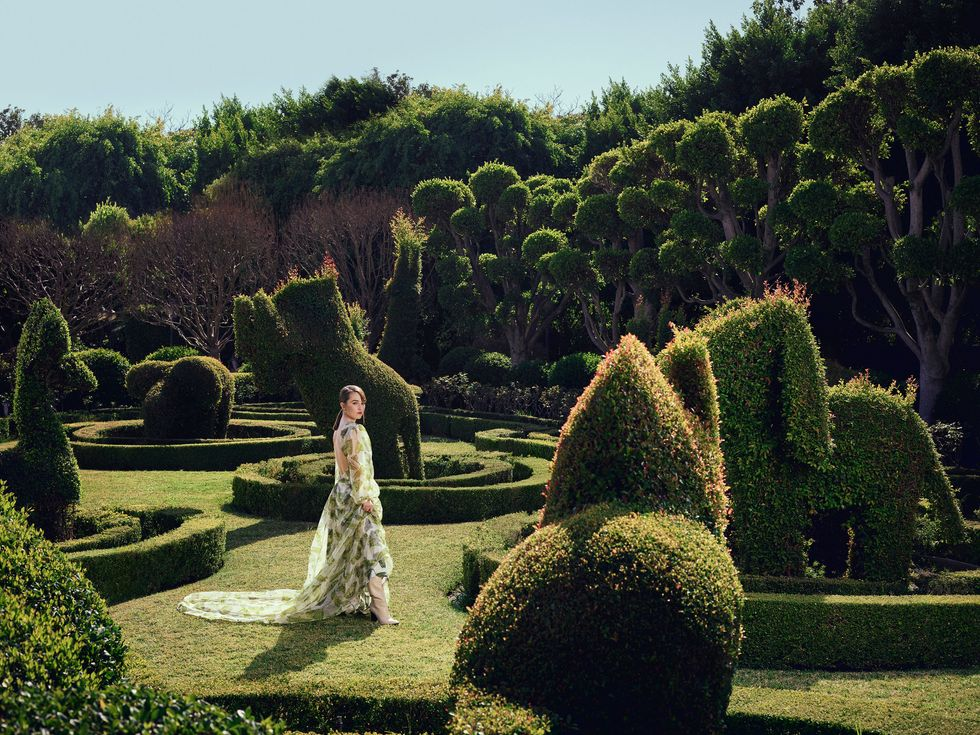 Actress Kaitlyn Dever wears a flowing butterfly print dress in a groomed topiary garden.