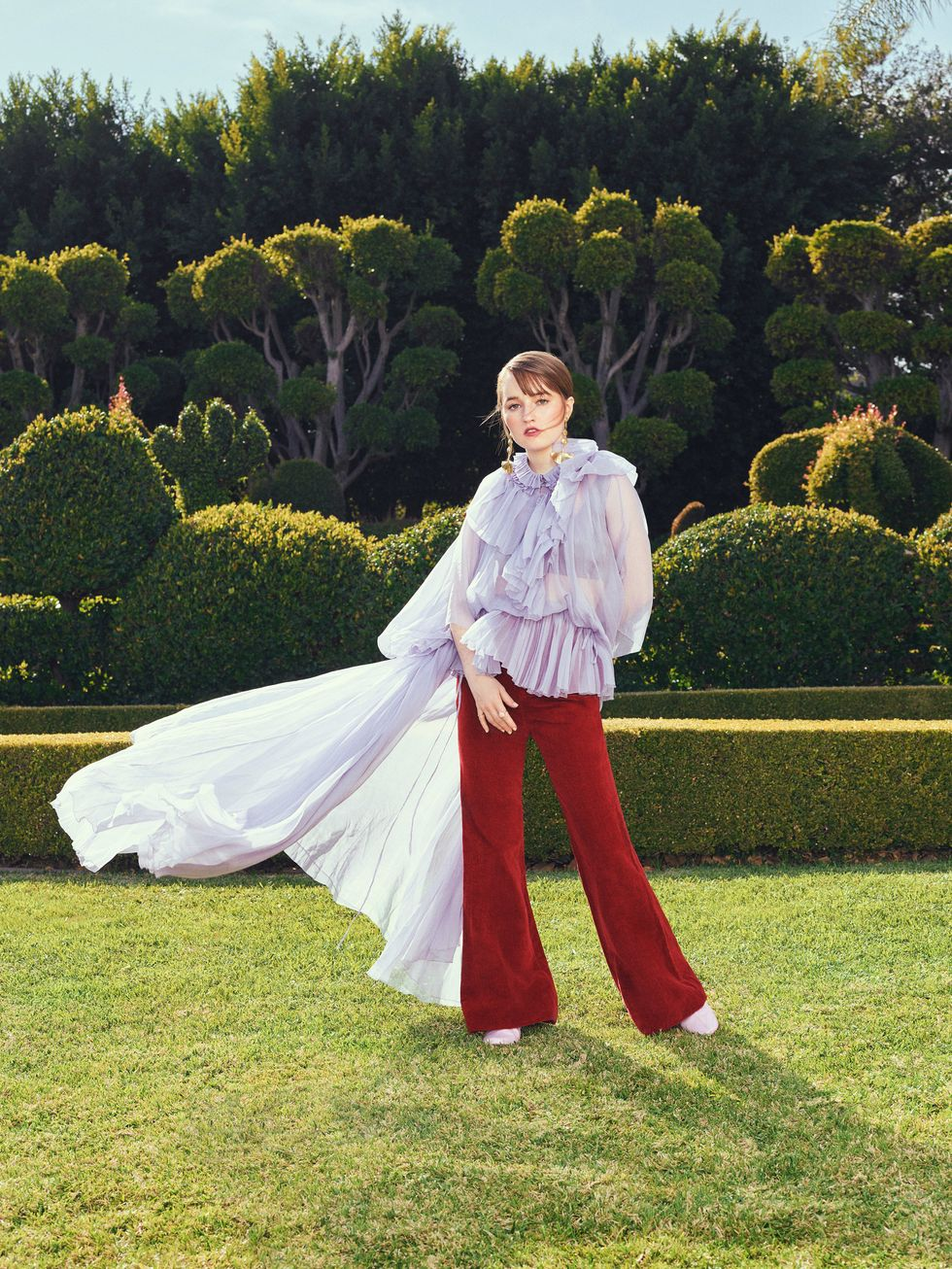 Actress Kaitlyn Dever Stands in a topiary garden wearing burgundy pants and long flowing lilac colored top.