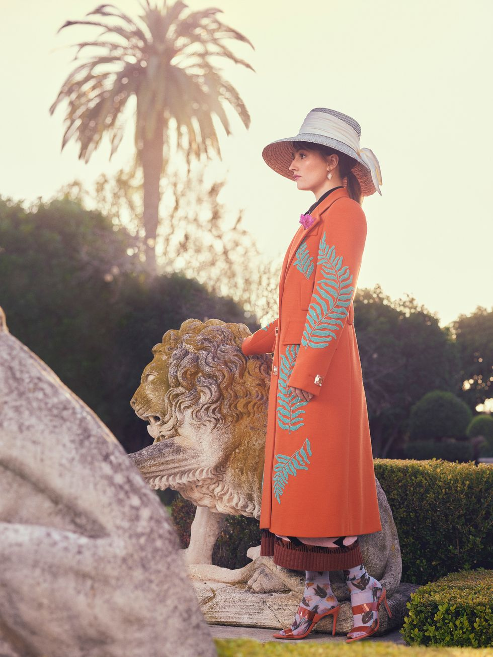 Actress Kaitlyn Dever stands next to a lion statue wearing an orange overcoat.