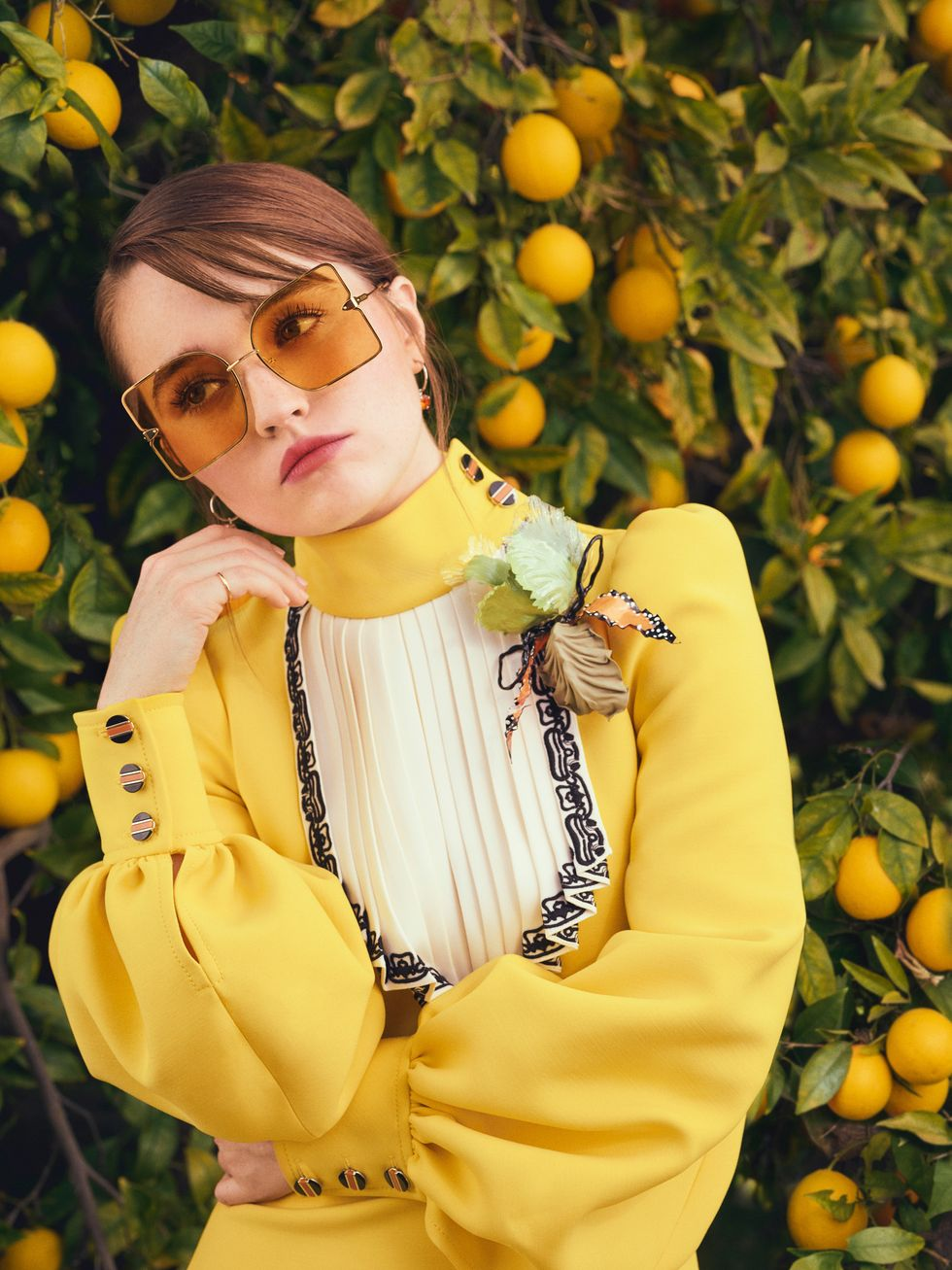 Actress Kaitlyn Dever wears a yellow dress as she stands in front of an orange tree full of fruit.