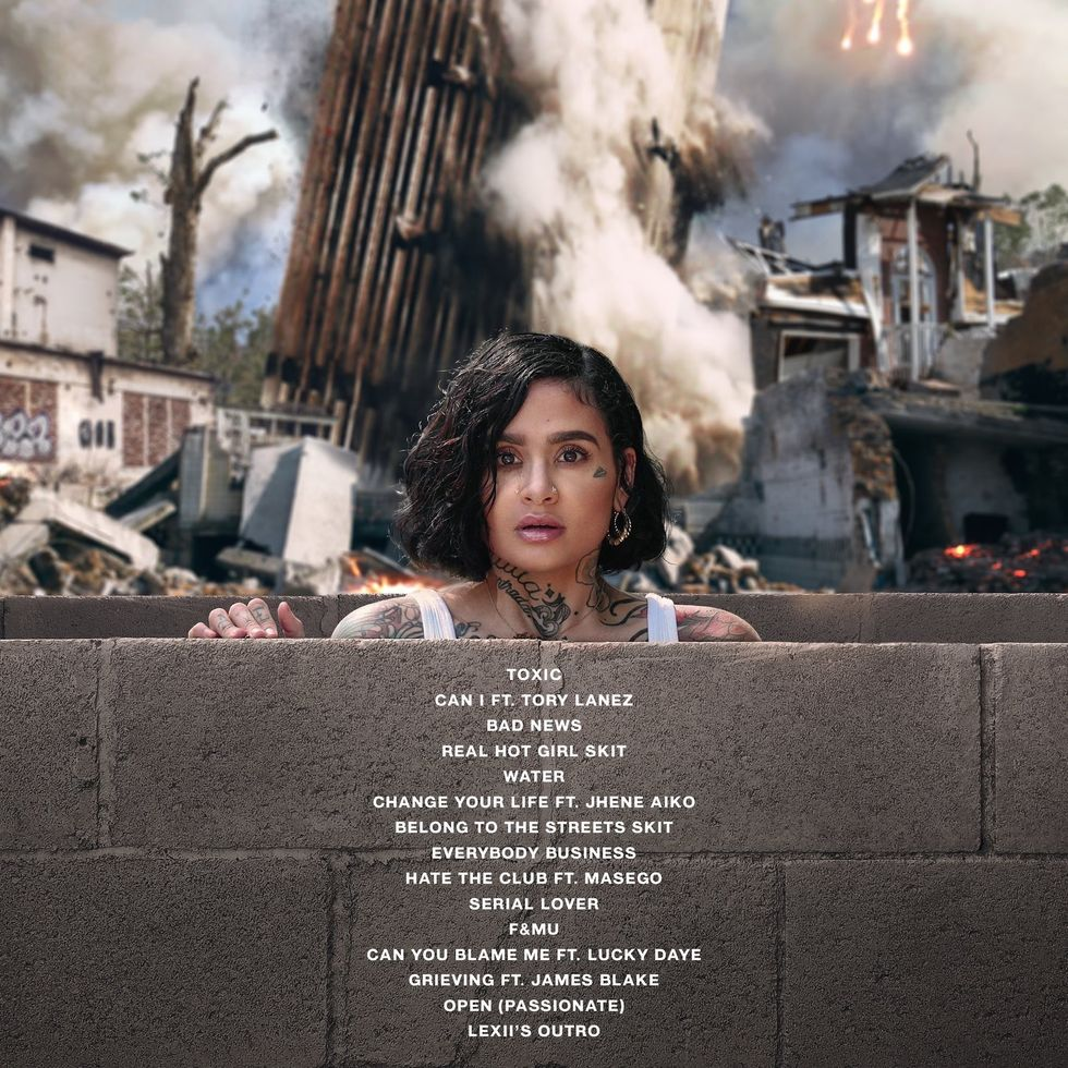 Kehlani looks over a brick wall and stares in disbelief as a destroyed building sits behind her