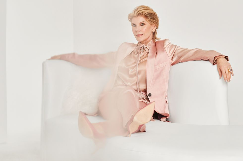 Christine Baranski sitting on a white sofa in a pink power suit.