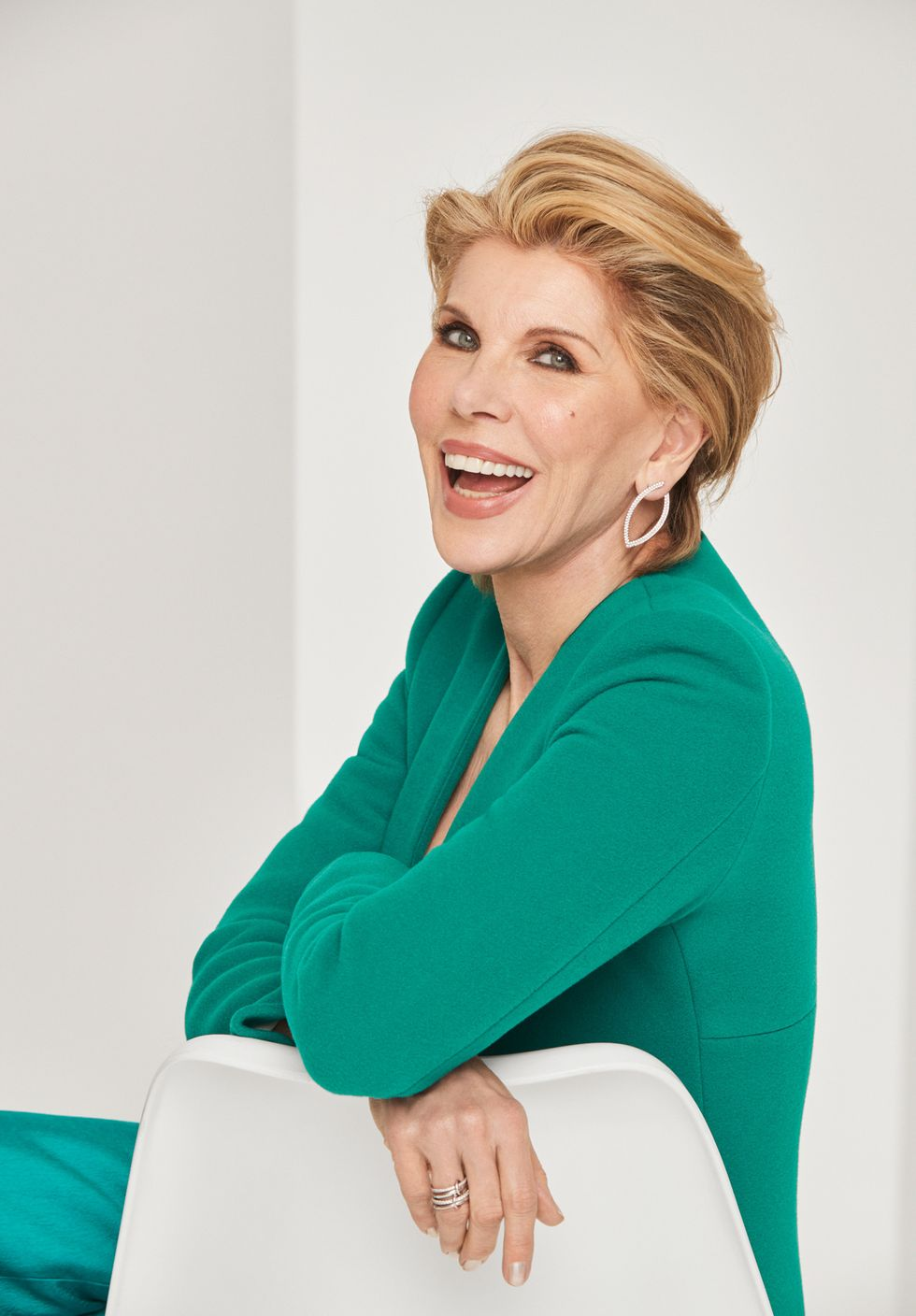 Christine Baranski in a green suit leaning against a chair.