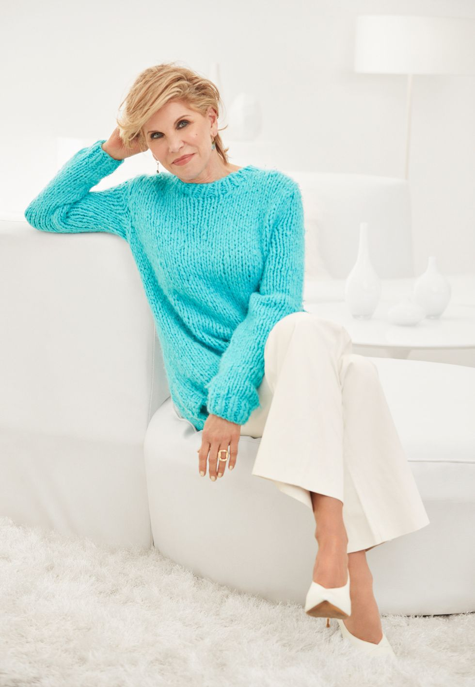 Christine Baranski in teal blue sweater and white pants.