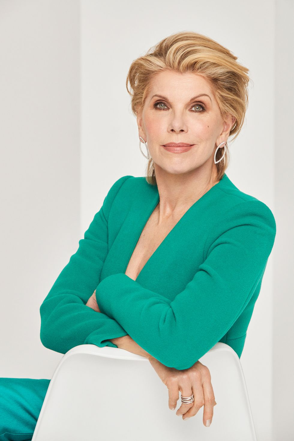 Christine Baranski in a green jacket leaning against a white chair.
