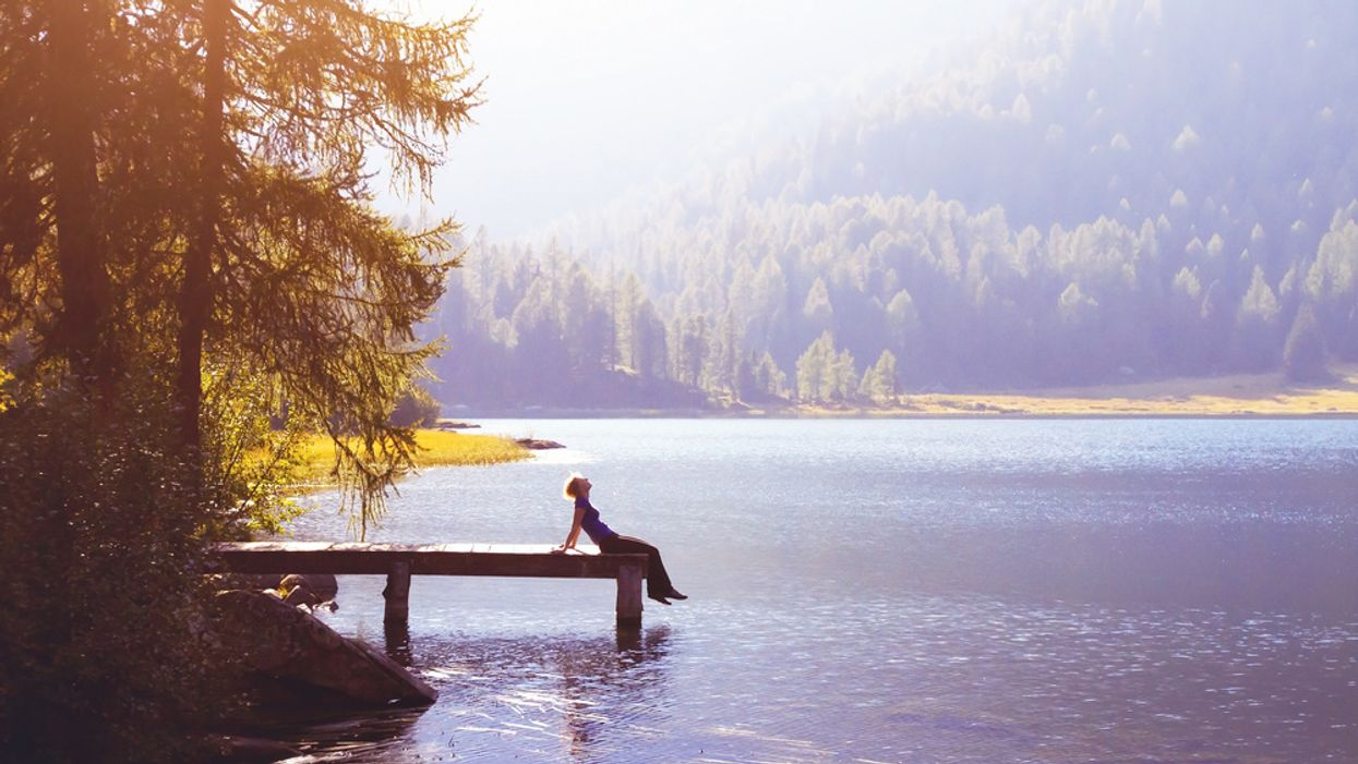 woman sitting alone on a dock by a lake in nature concept of ecotherapy nature therapy