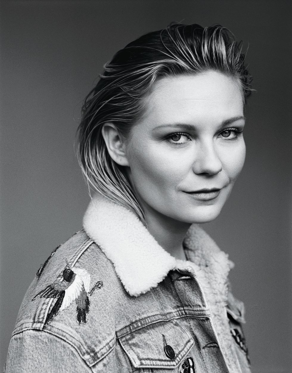 Black and white image of Kirsten Dunst smiling slyly at the camera.
