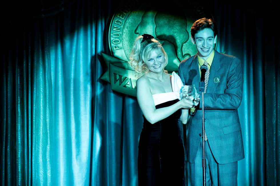 Still image of Kirsten Dunst and Theodore Pellerin accepting an award on stage.