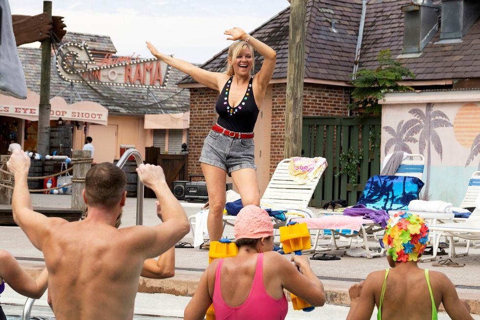 Still image of Kirsten Dunst teaching a water aerobics class.
