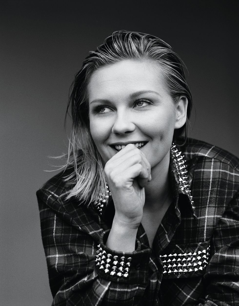 Kirsten Dunst wearing a plaid blazer with ornamental metal spikes.