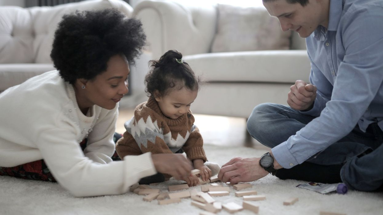 man and woman playing with baby and wood blocks