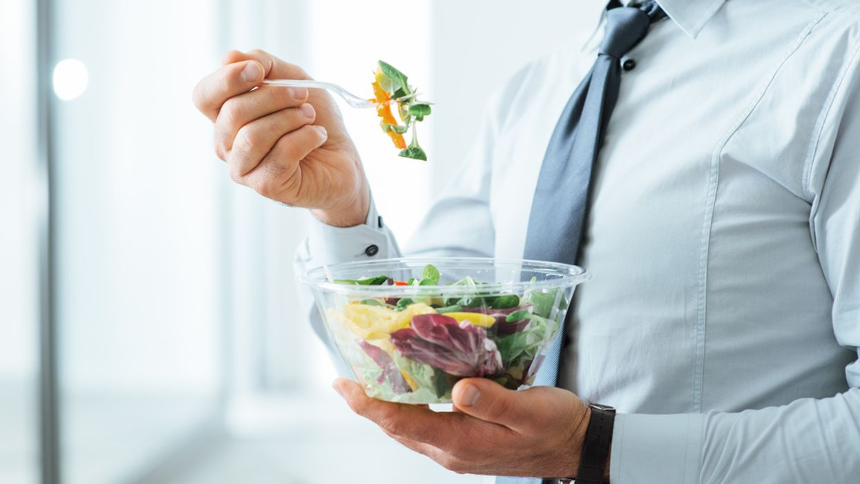 businessman in dress shirt and tie eating a salad at work