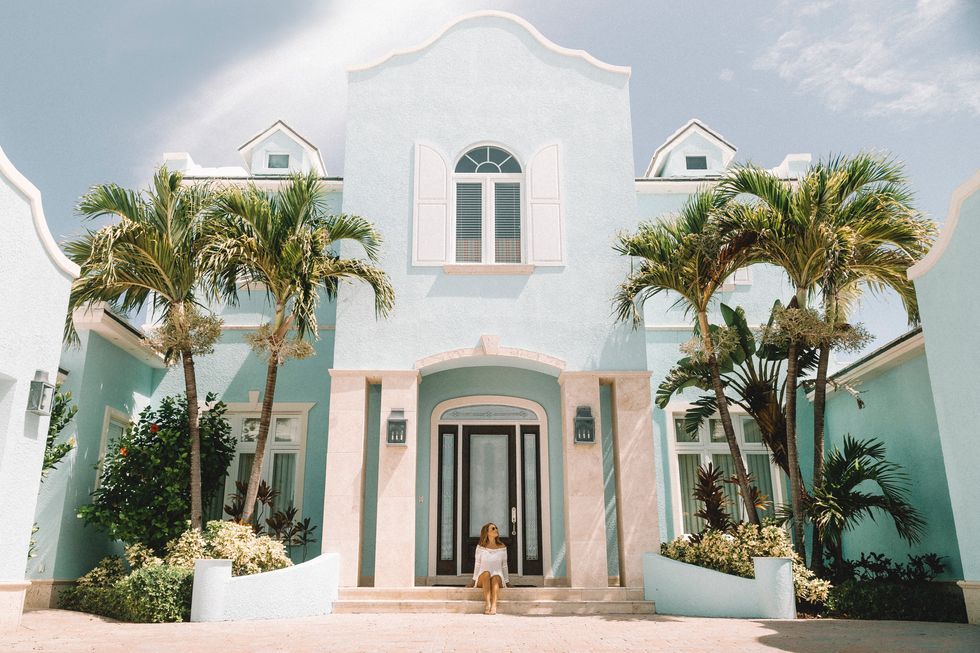 woman on front steps of California home with palm trees