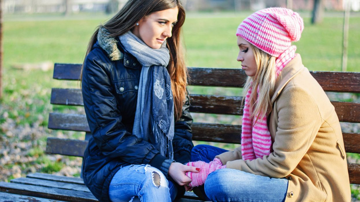 two women sitting on a bench talking after an arguement conflict resolution same-sex relationships