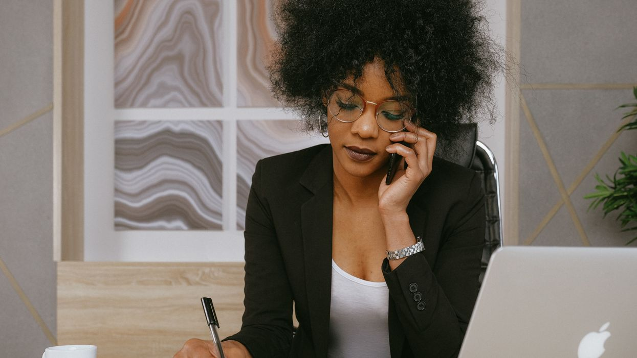 woman in a blazer holding a pen and talking on the phone