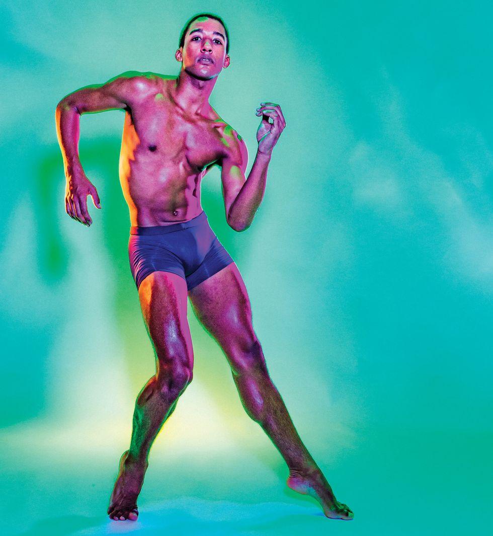 Watters, en short de vélo violet, pose en arc forcé avec ses bras à un angle, regardant directement dans la caméra, sur un turquoise transparent