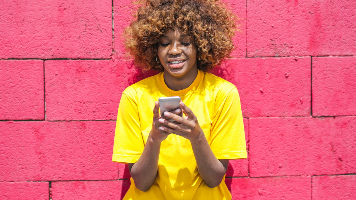 woman in yellow shirt against pink wall smiling at smartphone