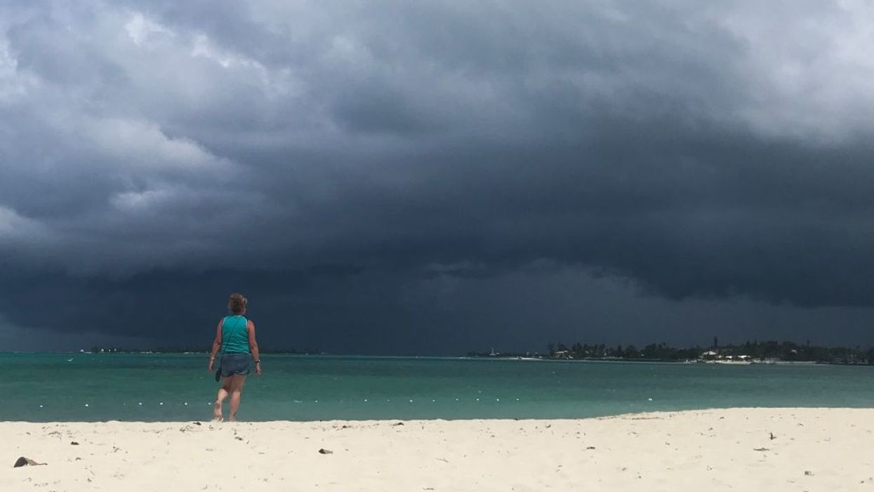 A woman walks on the beach as a storm approaches in Nassau, Bahamas