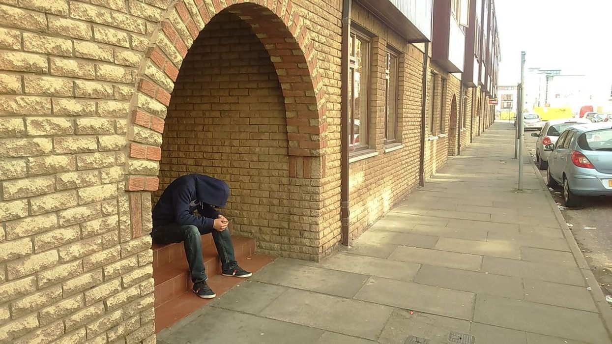 man sitting in doorway with his head down