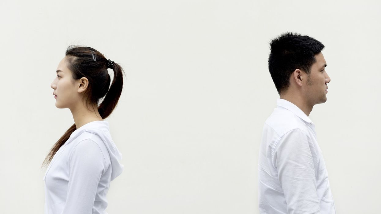 man and woman standing back to back