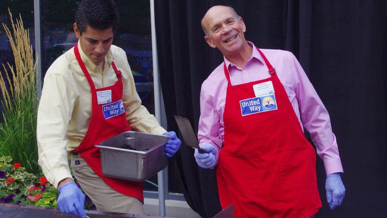two United Way volunteers cooking on a grill in red aprons