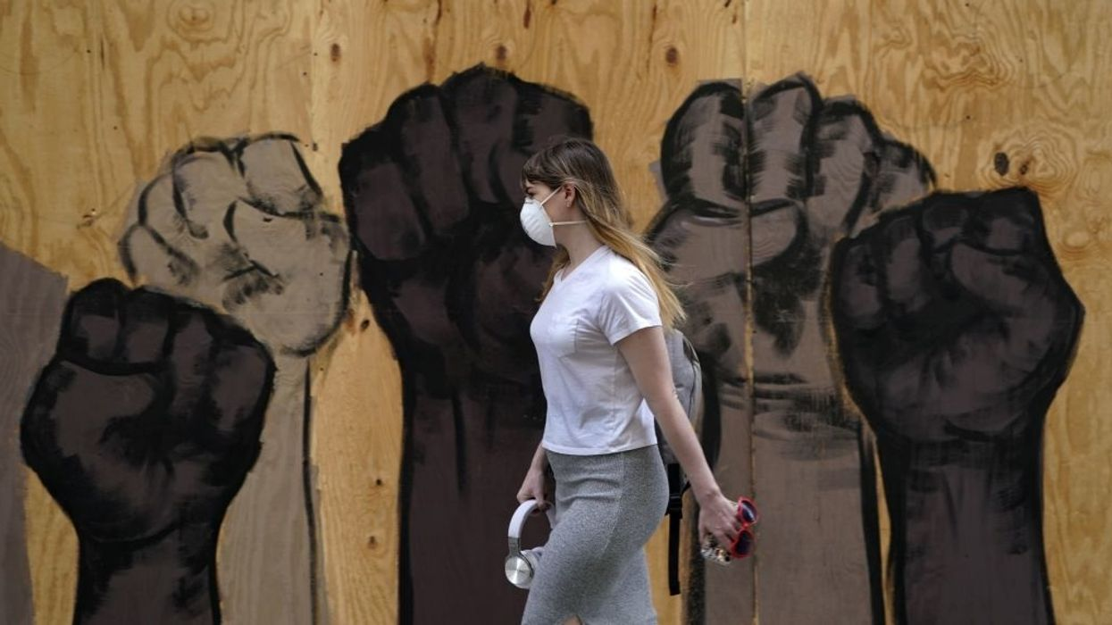 woman wearing facemask walks past mural of black fists