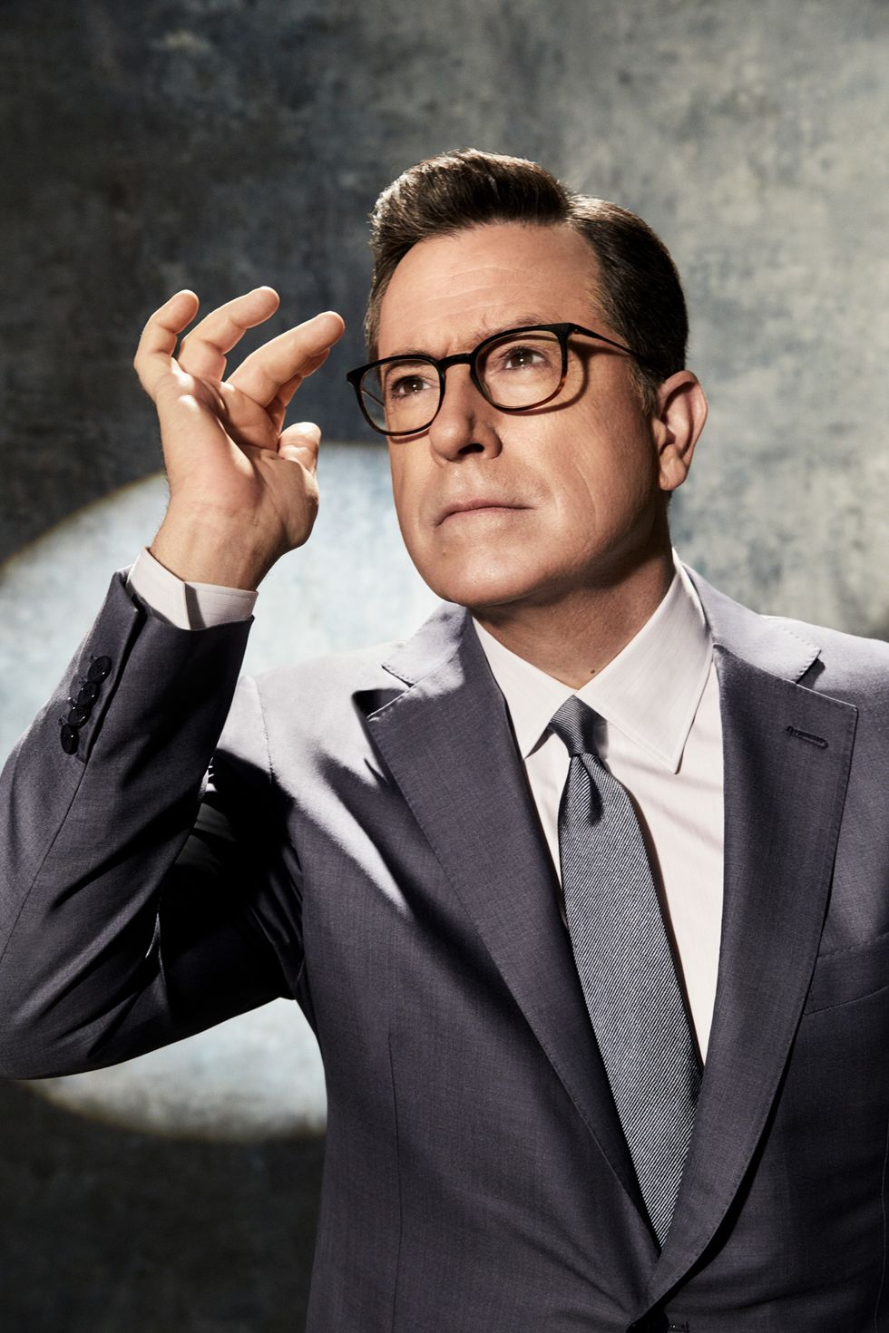 Stephen Colbert in a gray suit with a spotlight behind him.