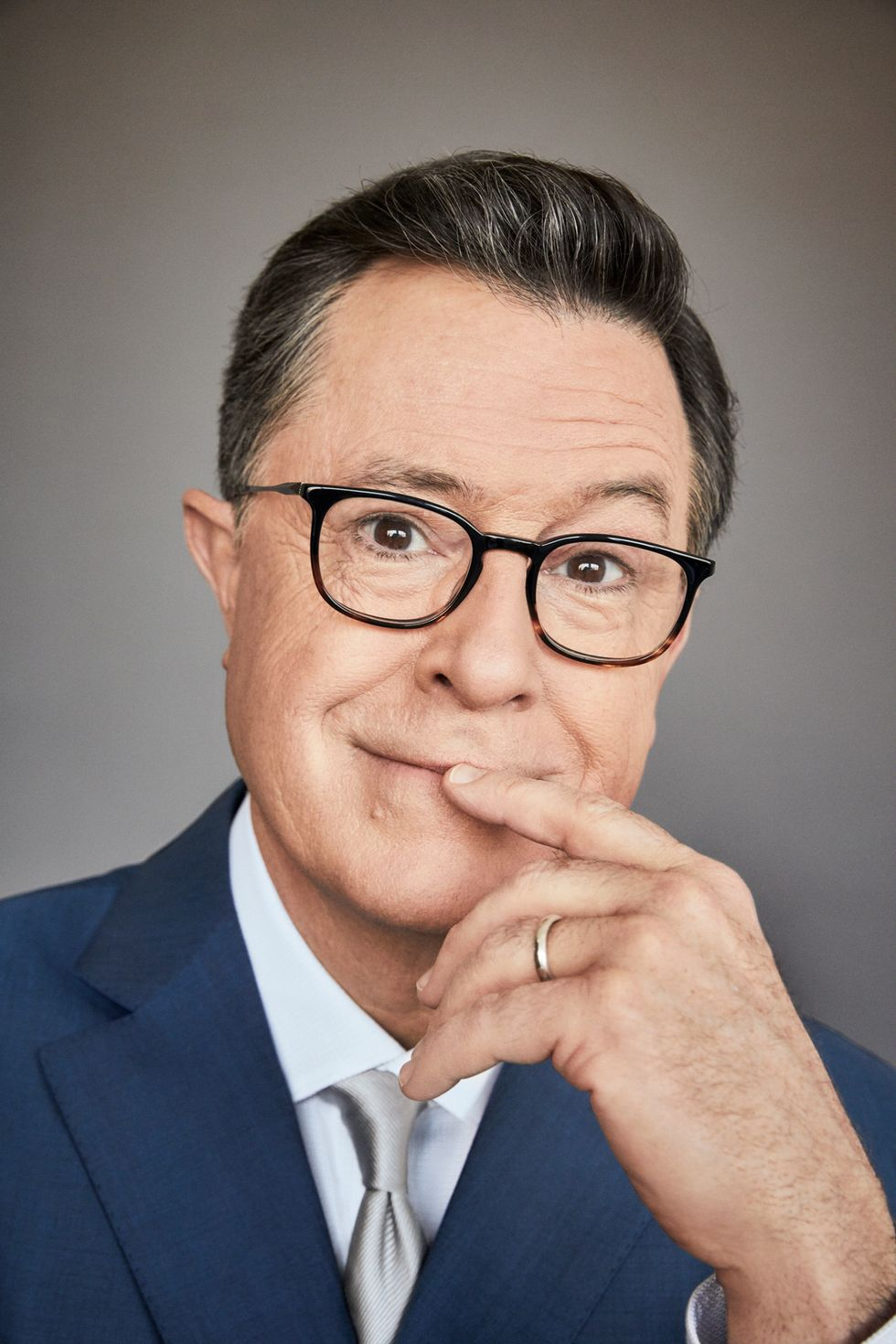 Close-up portrait of Stephen Colbert with his index finger to his lips.