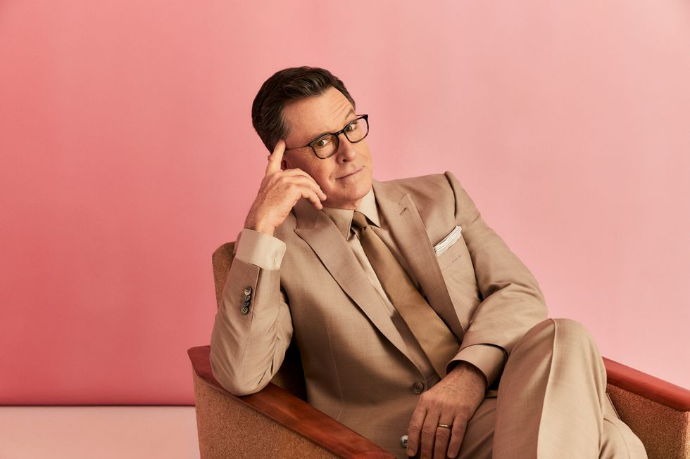 Stephen Colbert sitting in chair in a tan suit.