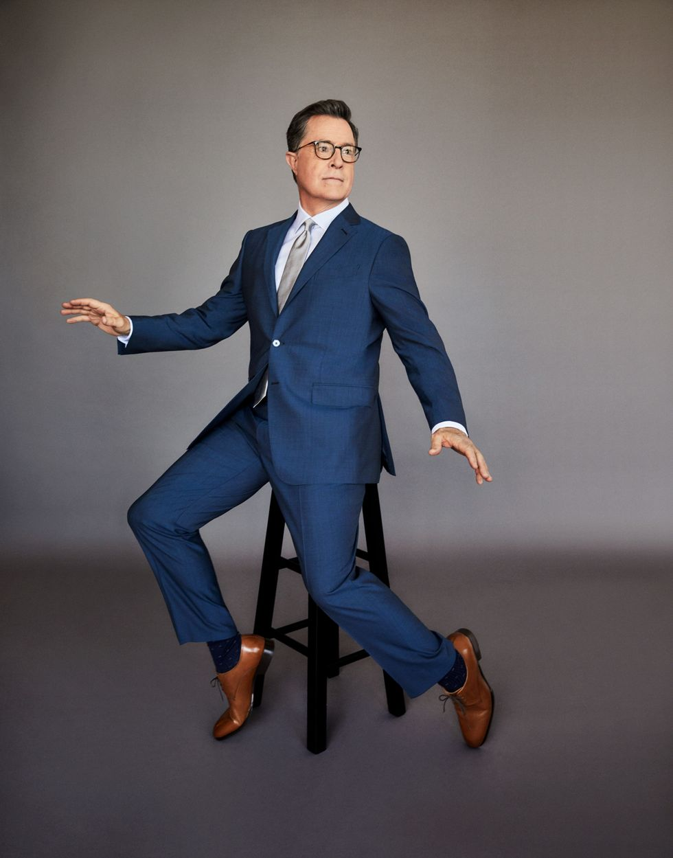 Stephen Colbert in a navy blue suit sitting on a stool.