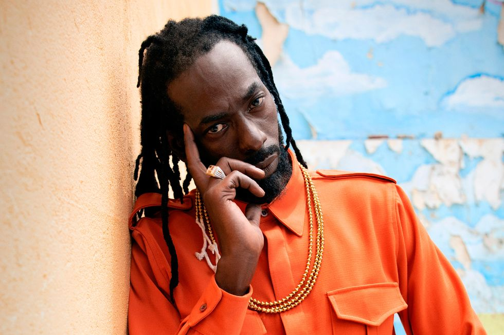 Buju Banton poses in front of a wall with a finger on his temple.