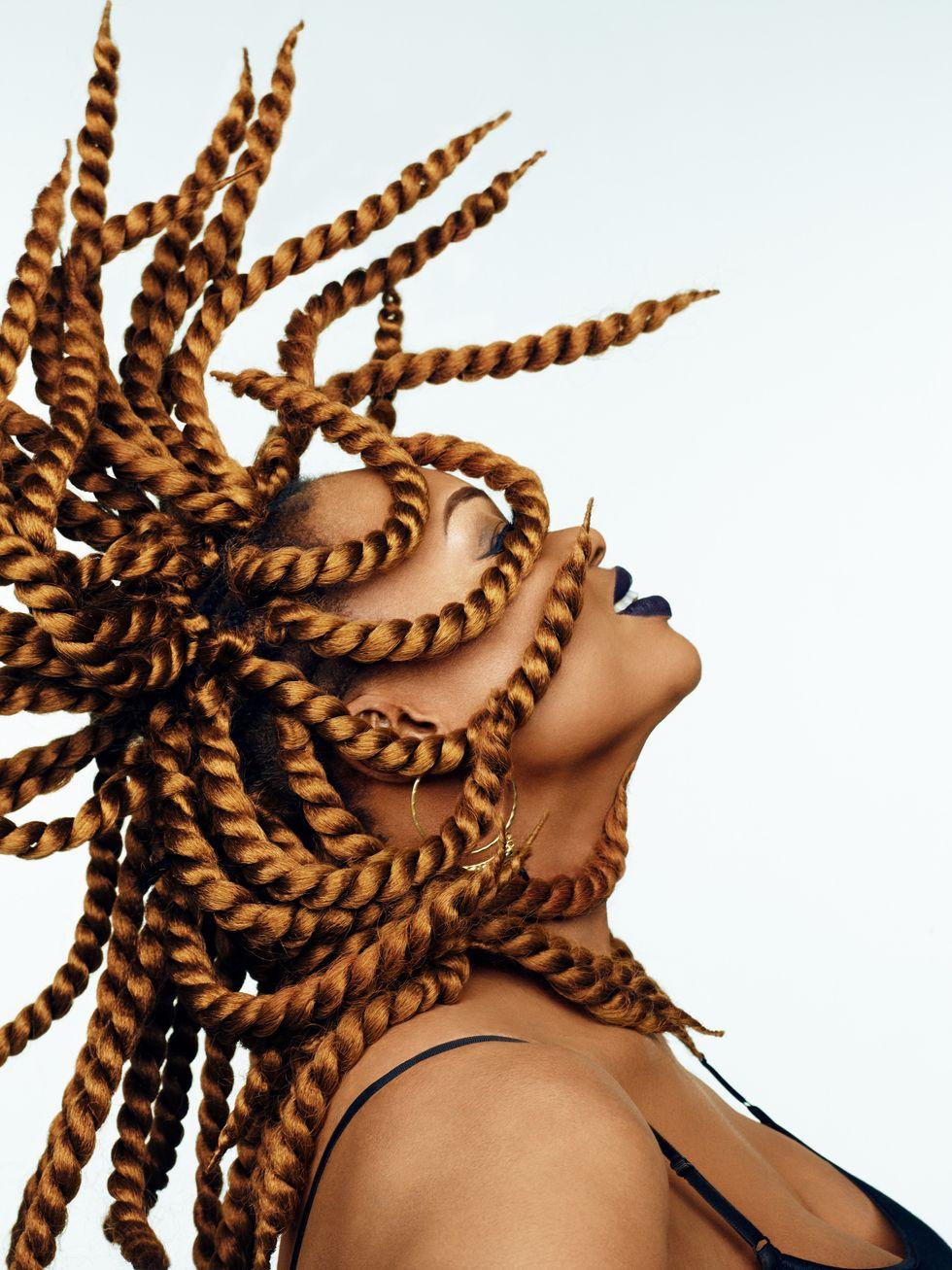 u200bOumou Sangaru00e9 throwing her head back, braids in the air.
