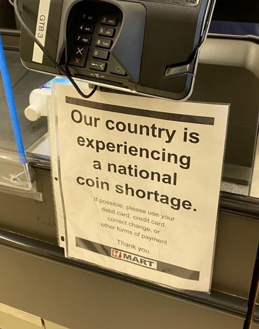 "Sign under cash register which reads, ""Our country is experiencing a national coin shortage. If possible, please use your debit card, credit card, correct change, or other forms of payment. Thank you."""