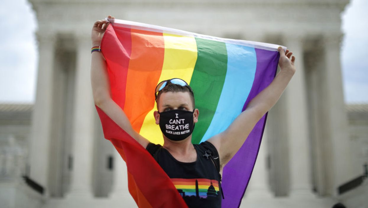 person wearing face mask holding pride flag