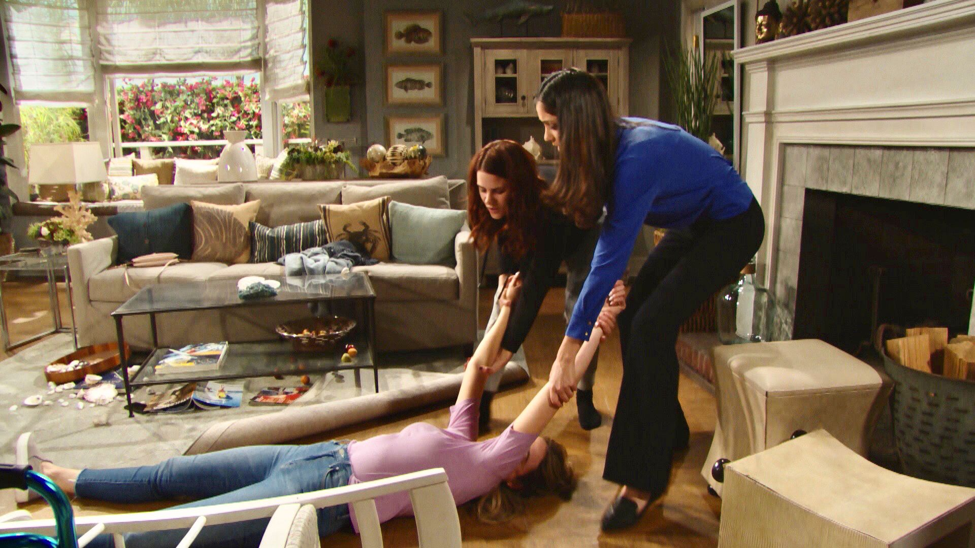 Katrina Bowden as Flo lies on her back on the living room floor, while Courtney Hope as Sally and Monica Ruiz as Dr. Escobar grasp her arms as they drag her toward the fireplace.