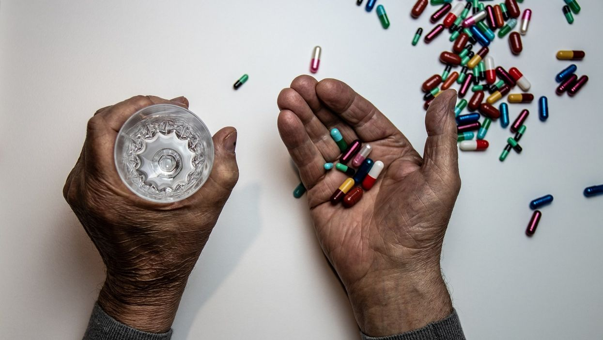 man holding various pills and a glass of water