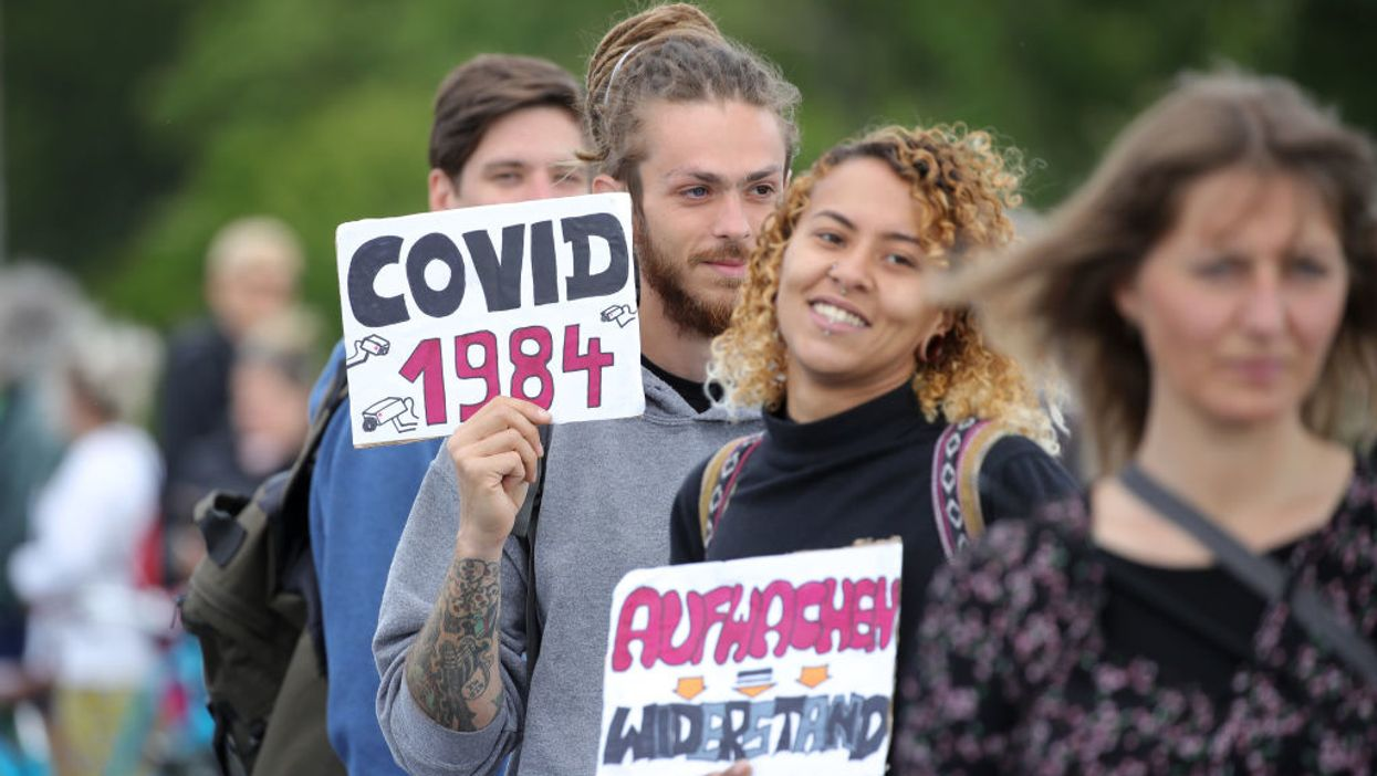 """protestor holding """"COVID 1984"""" sign"""