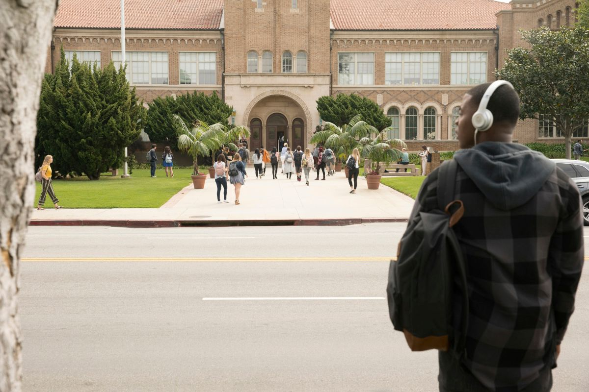 Daniela Ezra in front of a prestigious high school on TV show from The CW All American